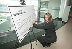 Ruth Hughs, Texas Workforce Commissioner representing Employers signs the ceremonial check presented at Collin College on Nov. 17.