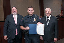 Officer Don Mewbourn (center) of the Collin College Police Department received a commendation for exemplary service in the line of duty from the college's Board of Trustees at their March 28 meeting. The commendation was presented to Officer Mewbourn by District President Dr. Neil Matkin (left) and Board Chairman and Founding Trustee Dr. Bob Collins.